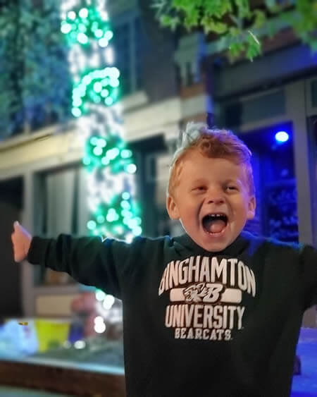 Cute child having fun in front of tree wrapped in green and white lights.